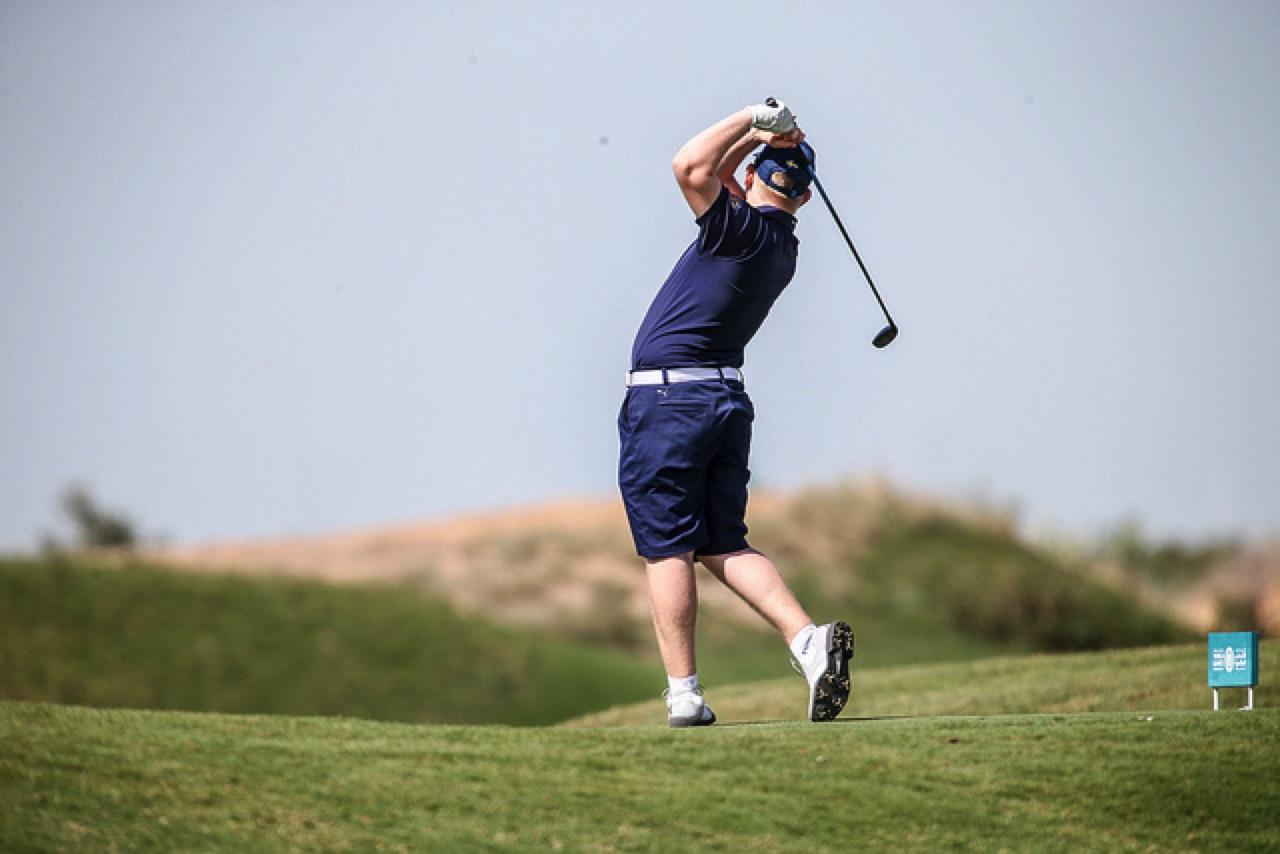 En golfspelare slår ut på en golfbana.
