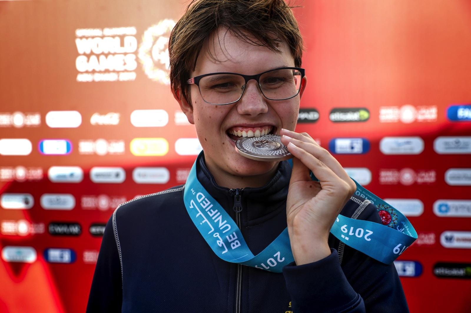 Rebecka Mårtensson står framför en sponsorvägg och biter i en silvermedalj.