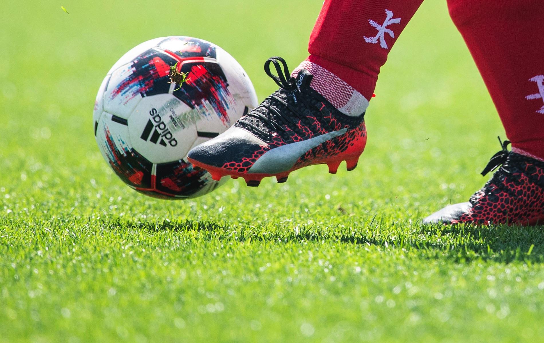 Närbild på en fotboll som en person sparkar på.