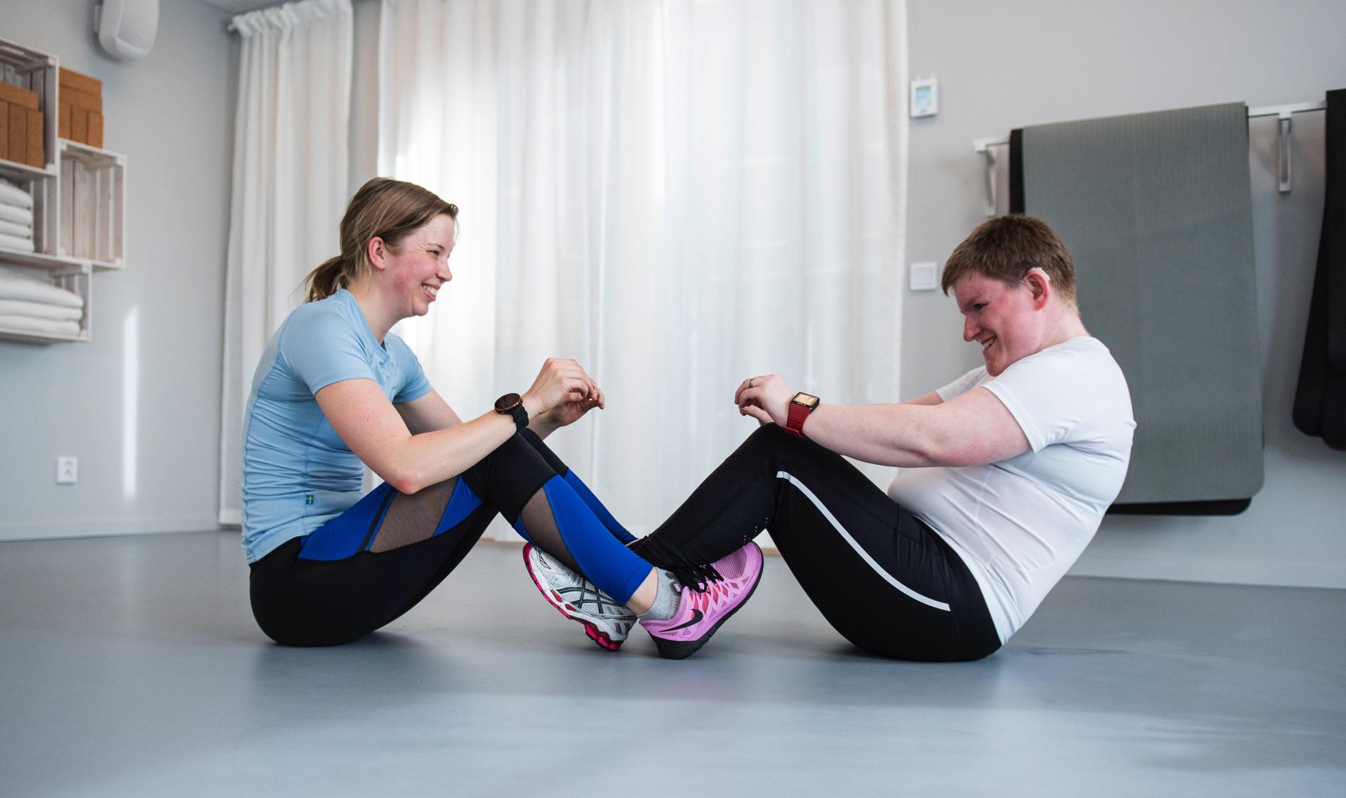 Johanna Oskarsson och Eva Dahlberg gör situps mot varandra på golvet i en yogasal.