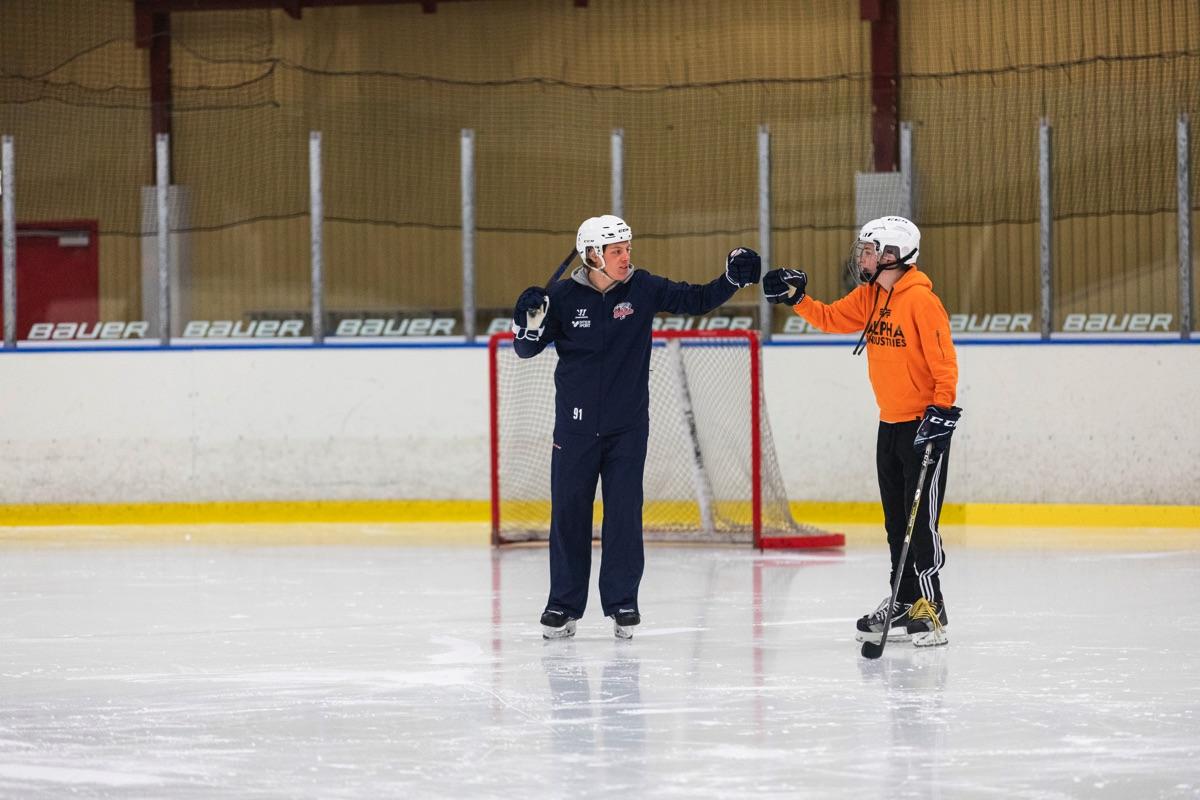Två ishockeyspelare fist-bumpar framför ett hockeymål.