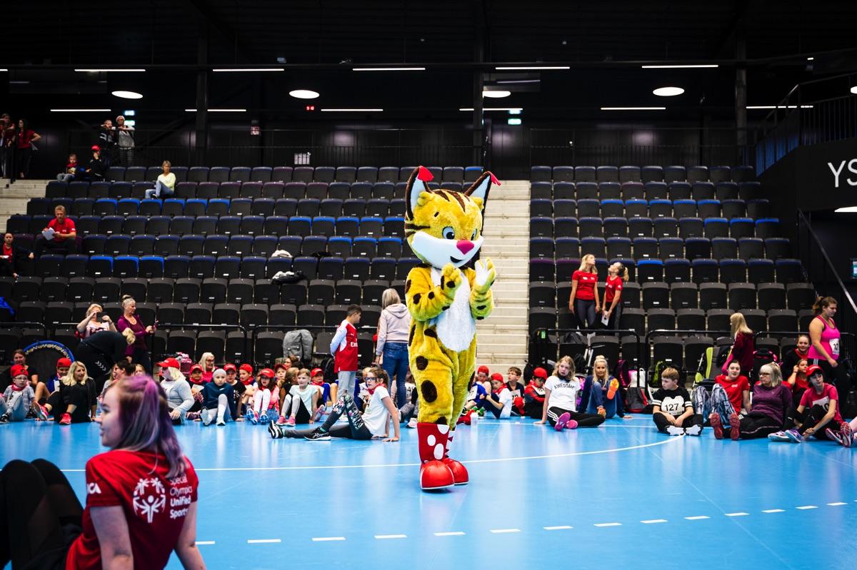 Special Olympics Sveriges maskot Speci-lo står i mitten av en idrottshall. Runt omkring sitter flera elever.