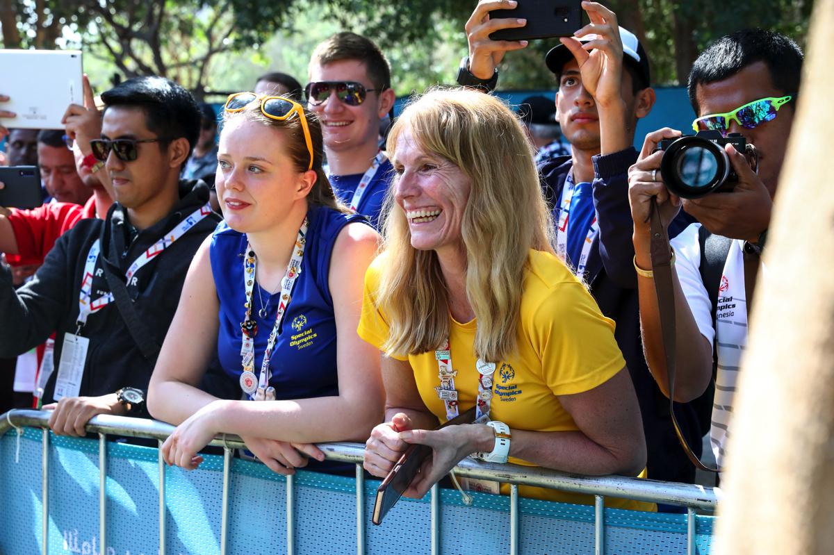 Eva Sundqvist, friidrottstränare och idrottsledare, prisas för sitt engagemang. På bilden står hon vid ett stängsel tillsammans med flera andra personer. Bilden är tagen i Dubai i samband med Special Olympics World Games 2019.