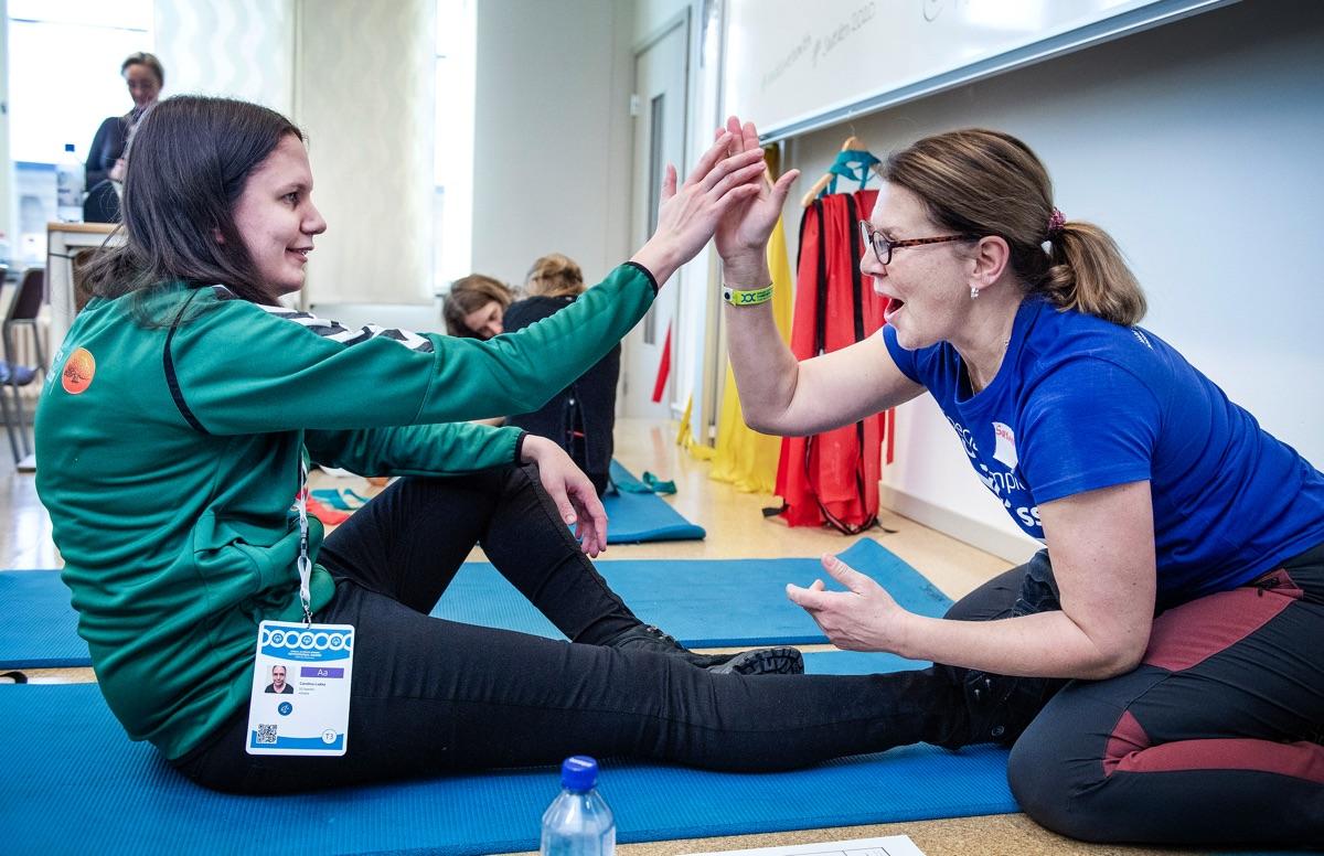 En volontär gör high five med en aktiv på en hälsostation inom Healthy Athletes-programmet.